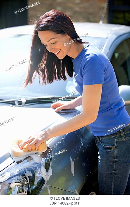 Woman washing car with sponge in sunny summer driveway