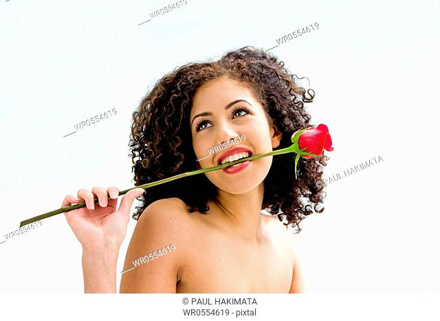 Sincere beautiful young woman with brown curly wild hair and bare shoulders biting rose, isolated