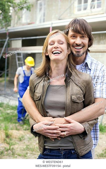 Young couple at site embracing, construction worker in background