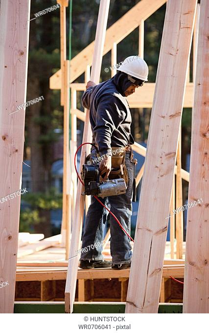 Carpenter with a nail gun working on rafters