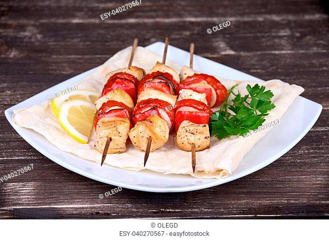 Tasty grilled meat and vegetables on skewer on plate