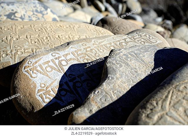 Mani wall (stones inscribed with a buddhist mantra) in the village of Tangge. Nepal, Gandaki, Upper Mustang (near the border with Tibet)