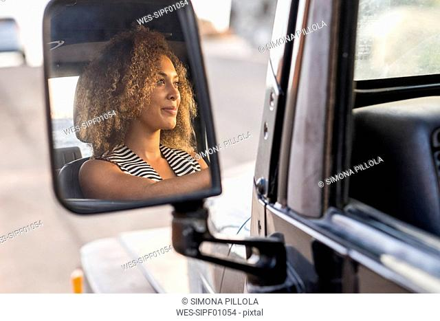 Mirror image of smiling young car driver