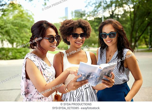 happy women with city guide on street in summer