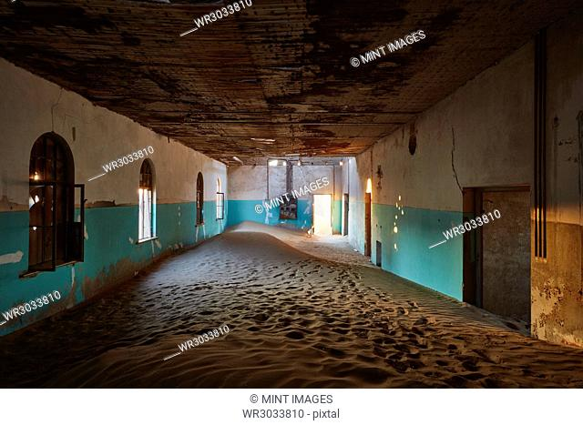An abandoned building with boarded up windows, and shafts of sunlight lighting up the drifting sands and remnants of wall coloured green