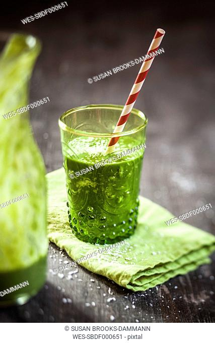 Glass of spinach smoothie with coconut milk, lemon- and orange juice and banana on napkin and wooden table