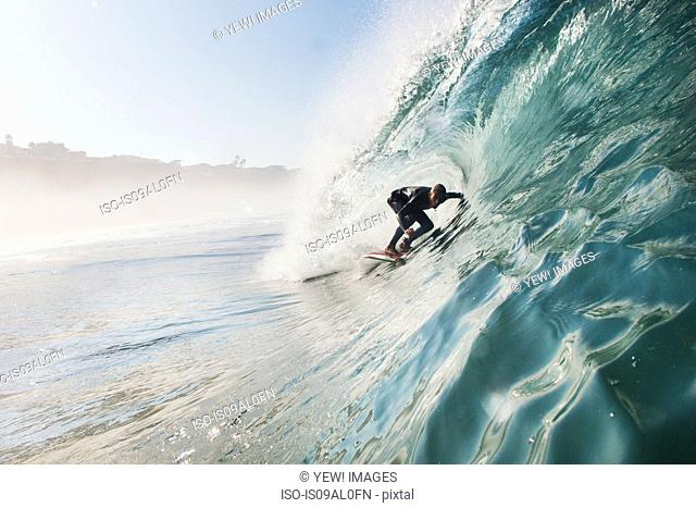 Mid adult man surfing rolling wave, Leucadia, California, USA