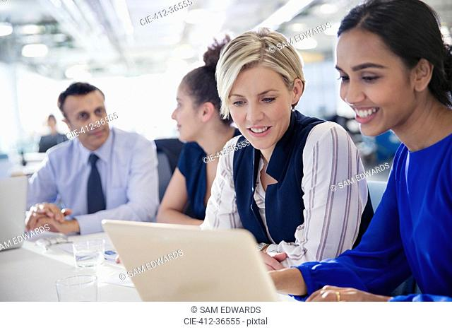 Businesswomen working at laptop in office meeting
