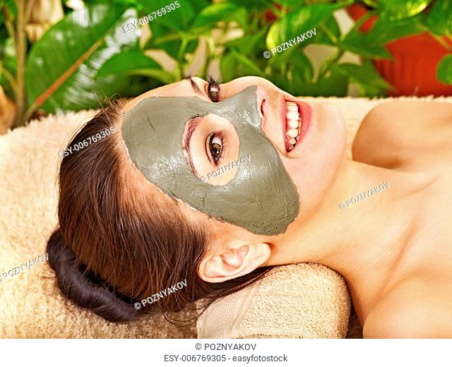 Woman getting facial mask in tropical beauty spa