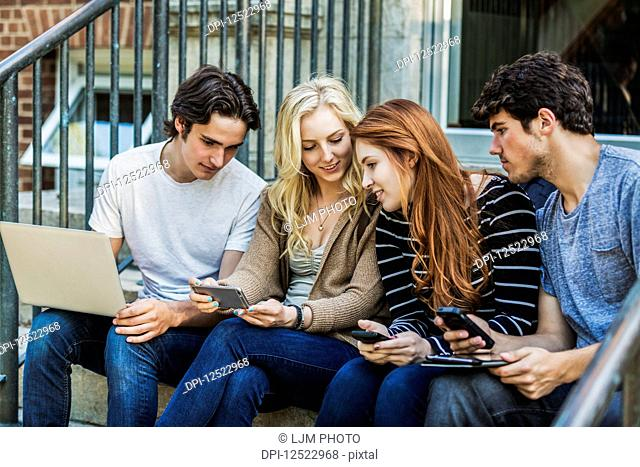 Four students sitting in a row on a step using their technology on the university campus; Edmonton, Alberta, Canada