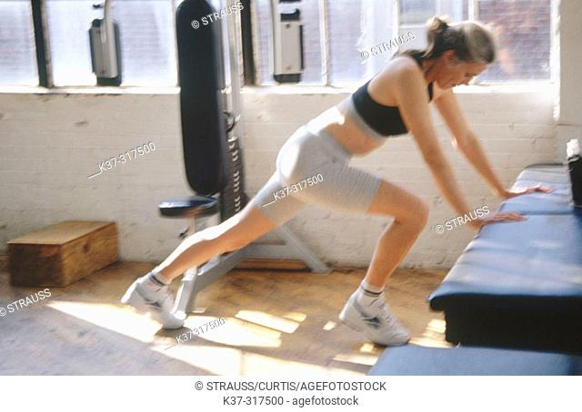 Mature woman exercising in health club