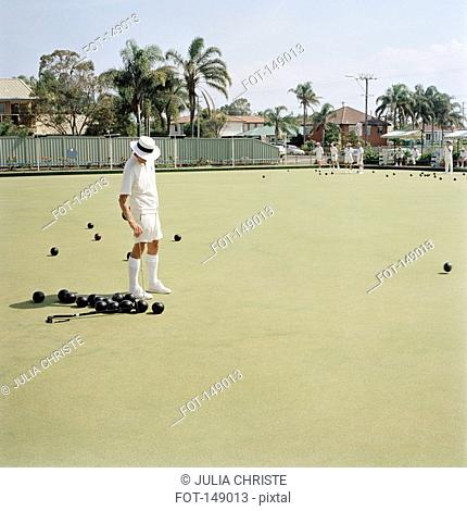 An old man hurling a bocce ball