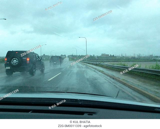 A black SUV enters a highway in heavy rain, view from the passenger's side, Quebec, Canada