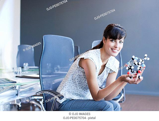 Businesswoman holding molecule model in conference room