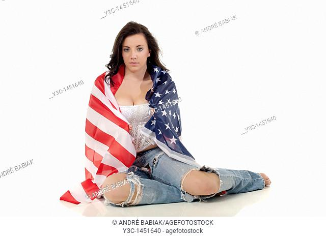 Young woman in ripped jeans wrapped in american flag