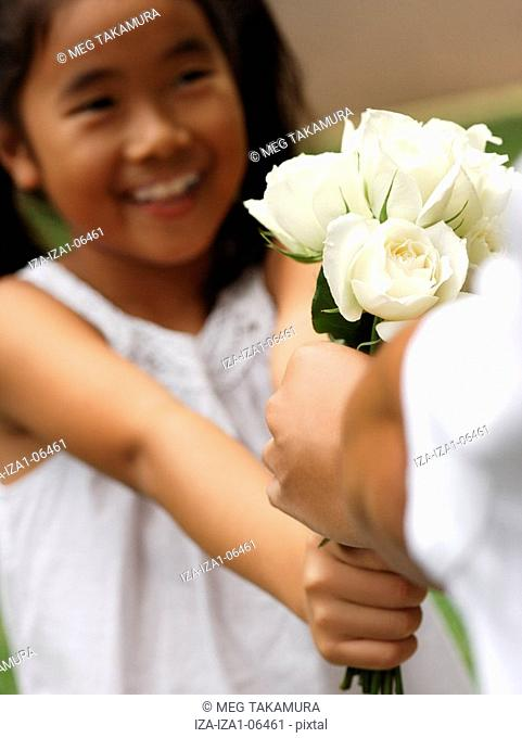 Close-up of a girl giving a bunch of white roses to a person