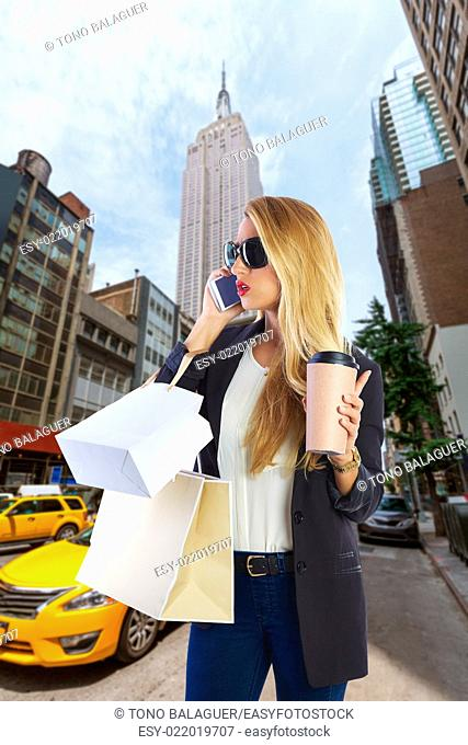 Blond girl shopaholic talking phone in fifth 5th avenue on New York Manhattan Photomount
