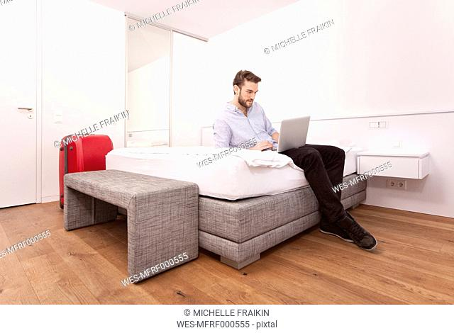 Young man sitting on a hotel bed using laptop