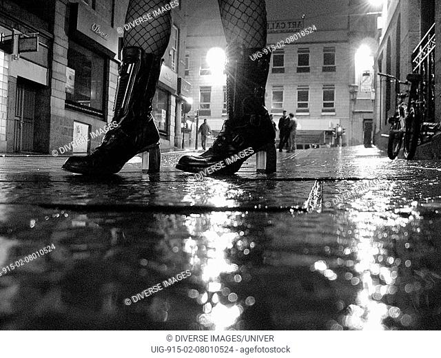 The wet cobbled streets of Aberdeen with a lady of the night's stockings and boots in view, UK 2005