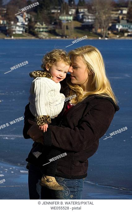 A woman holds her daughter at the beach