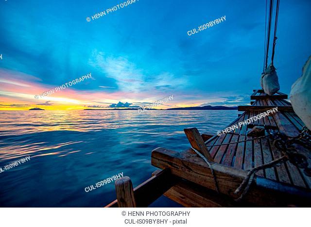 Traditional ship sailing toward sunset in Raja Ampat, Sorong, Nusa Tenggara Barat, Indonesia