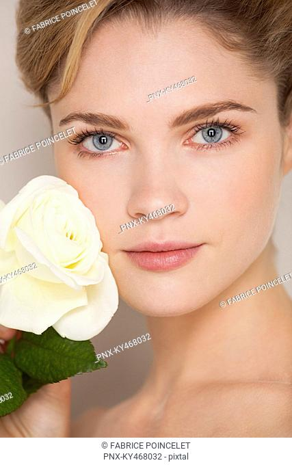 Beautiful woman touching rose on her face
