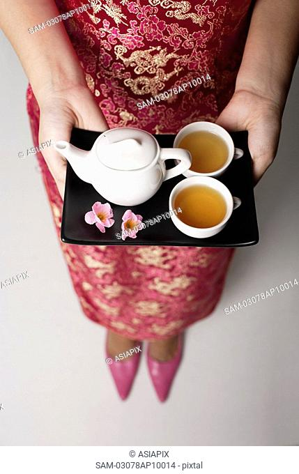 close up of woman wearing pink cheongsam holding tray with tea