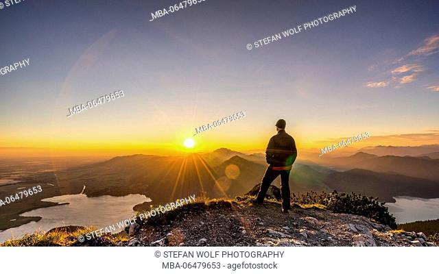 Hiker enjoys the view at the Herzogstand at sunrise, Bavarians, Germany