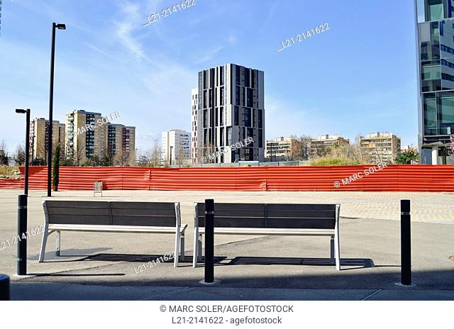 Two benches, red aluminium wall, fence, buildings, blue sky. Plaça Europa, Plaza Europa, District VII, Gran Via, Hospitalet de Llobregat, Barcelona province