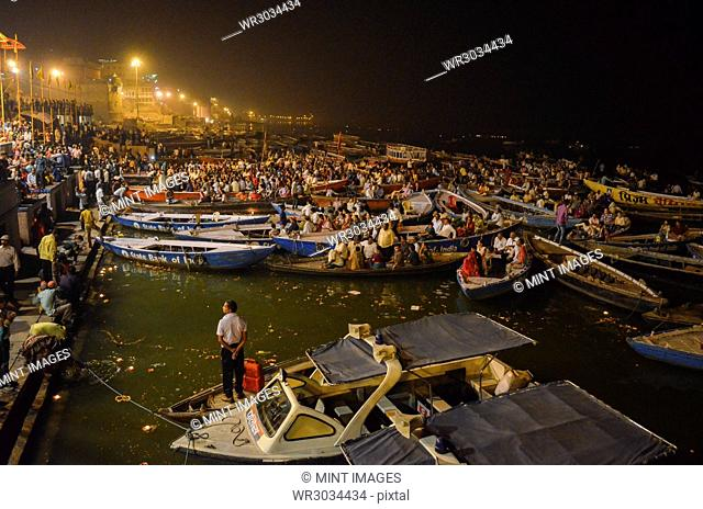 large group of people on boats moored at night on the Ganges at Varanasi, India