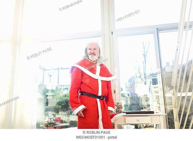 Smiling bearded mature man wearing Santa costume