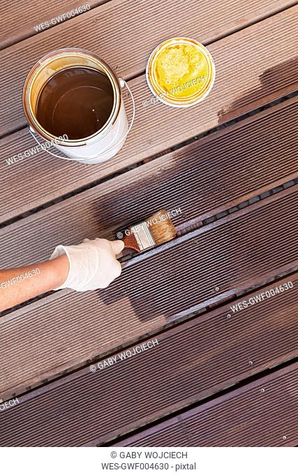 Woman's hand applying glaze with brush on floorboards