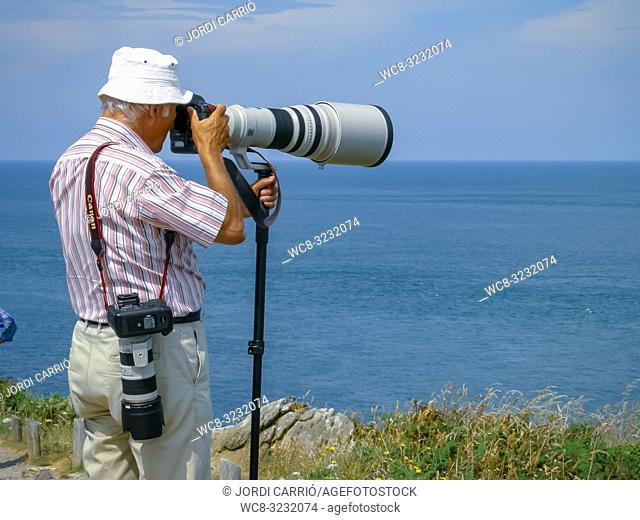 CANCALE, BRITTANY, FRANCE: Photographer photographing birds of Landes Island from Cape Grouin