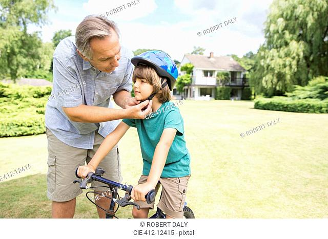 Grandfather adjusting bicycle helmet on grandson