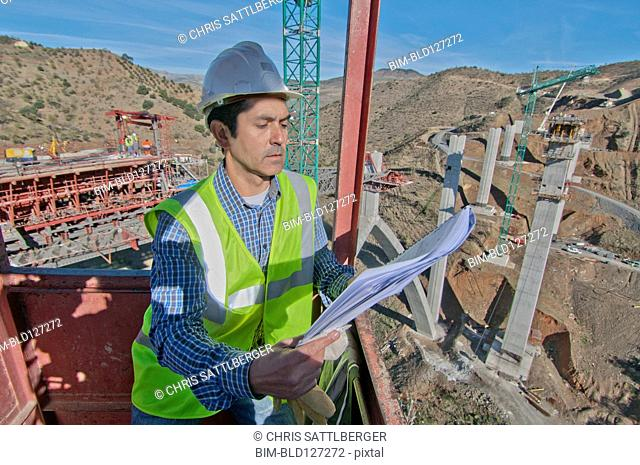 engineer with plans at bridge construction site
