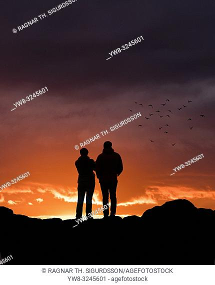 Couple watching the sunset at Grotta, Reykjavik, Iceland