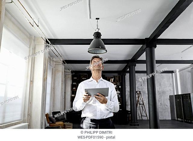 Mature man using digital tablet in loft flat