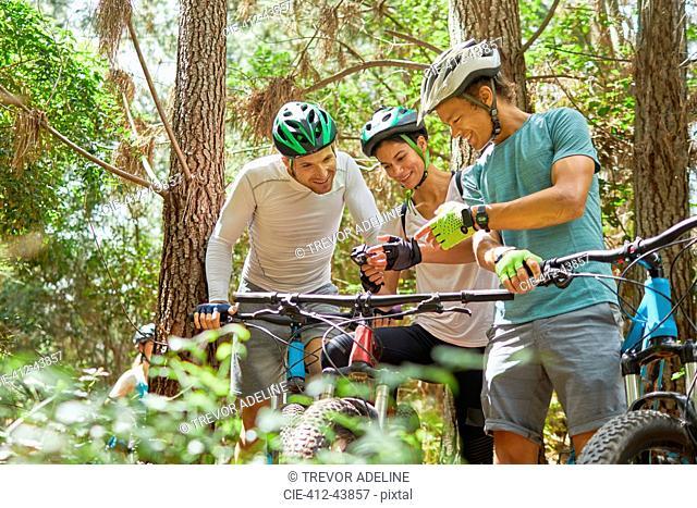 Friends mountain biking, using wearable camera in woods