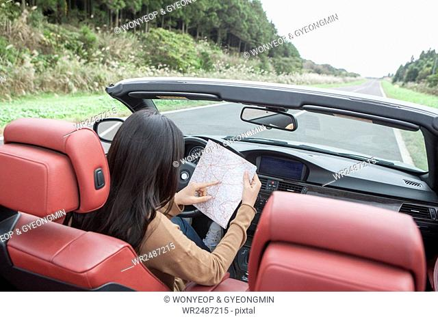 Back of young woman reading a map in a car
