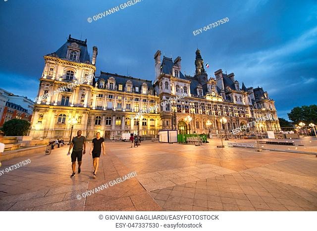 PARIS - JUNE 2014: Hotel de Ville at night with tourists. Paris attracts 30 million people annually