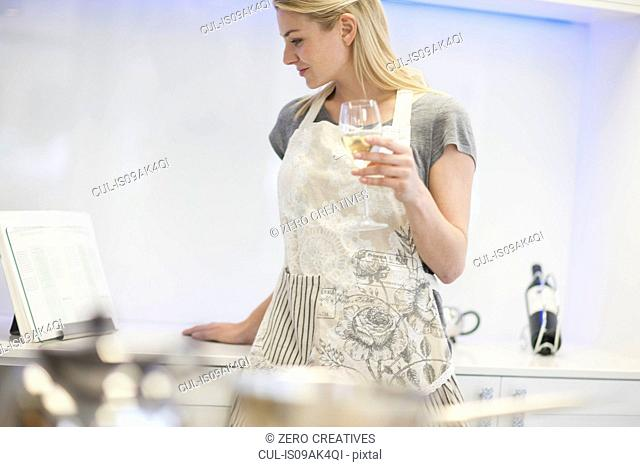 Young woman drinking glass of white wine whilst reading recipe book in kitchen