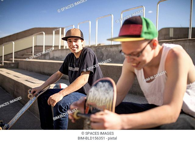 Caucasian men with skateboards sitting on steps