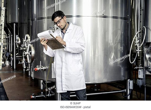 Brewer in brewery wearing lab coat writing on clipboard
