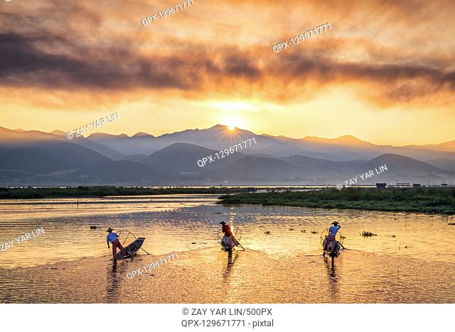 Three fishermen at sunrise in Inle Lake, Myanmar