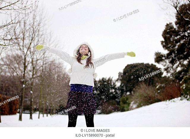 A young woman standing in the snow with her arms outstretched