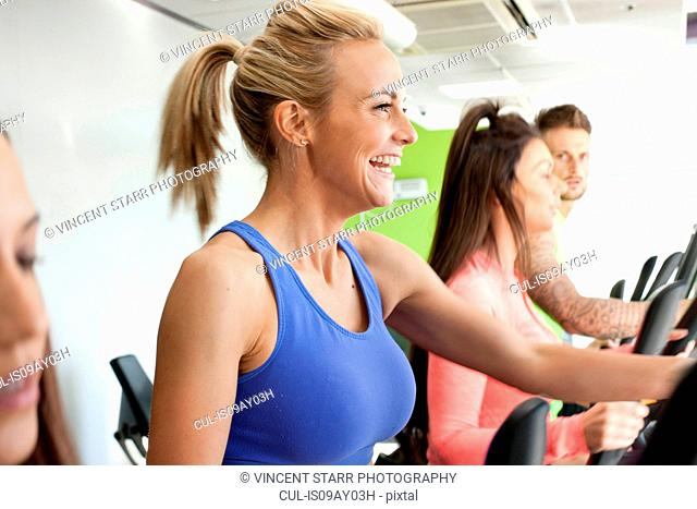 Woman in gym using exercise machine smiling