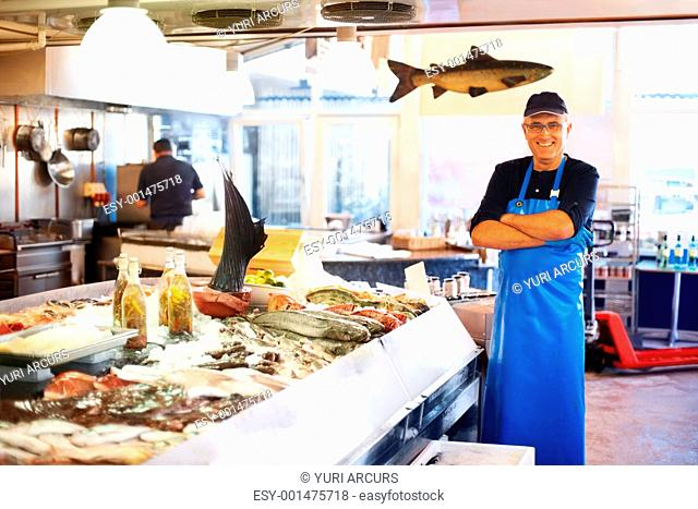 Happy fishmonger standing in market with his arms folded