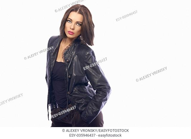 Young dark-haired girl in stylish clothes posing in front of camera. The girl is very cute and has a model appearance and a good slender figure