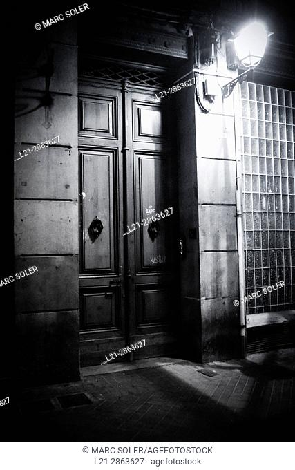 Closed doors. Entrance of a house and streetlight lit at night. Barcelona, Catalonia, Spain