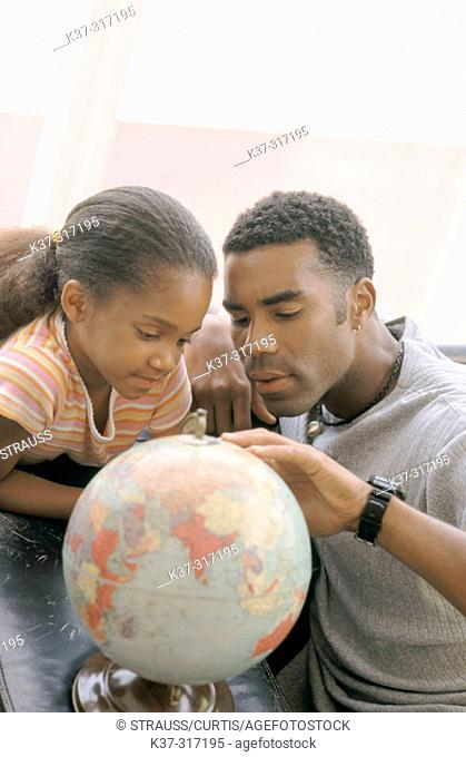 African-American father and daughter looking at globe